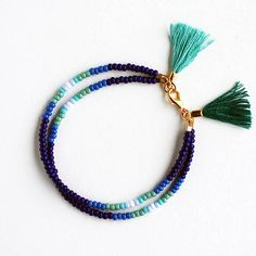 This listing is for ONE double strand bracelet in blue ombre with two tassels: one in aqua and one in peacock green color. Details: - made to order: 2-3 business days processing time, - mix of glass seed beads, - cotton tassels, - gold plated metal findings, - approx. 7.5 L All Felt