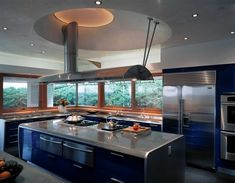 modern blue and inox kitchen with island and many windows for the master chef