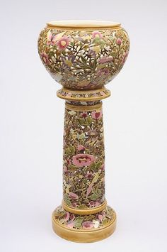 A Zsolnay Pécs openwork jardiniere and stand: of circular form and decorated with brightly coloured flowers, foliage and butterflies in pink, purple, green, mustard and gold, blue backstamp, impressed Zsolnay Pécs with model no. 2836, circa 1888.