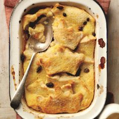Bread and butter pudding in a baking dish with a spoon removing one portion