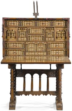 A Spanish parcel-gilt bone inlaid walnut bargueño 17th century the fall-front mounted with velvet-backed pierced metal lozenges, opening to reveal an architectonic interior with fourteen various short drawers and two cupboard doors, on a 19th century carved walnut stand