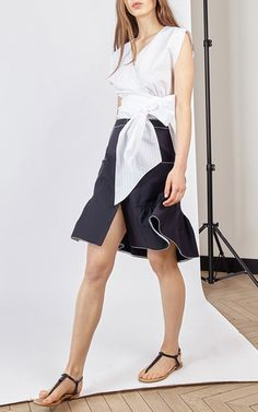 This **Alexis Mabille** Crop Wrap Blouse features a v-neckline, cap sleeves, and a fitted wrap waistband.