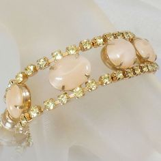 This #vintage yellow rhinestone cabochon bracelet is just gorgeous!  It features a gold tone bracelet with two rows of pale yellow rhinestones on either side of marbled oval... #etsy #antiques #jewelry #jewellery #shopping #easter #spring #wedding #prom