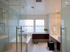 Why go to a spa when you can create one in your home? Follow the glass walls of the walk-in shower and you'll find a spacious two-person bathtub. Glass wall tiles and stone floors complete this modern bathroom, and privacy films on the windows brighten the sanctuary, while maintaining complete solitude