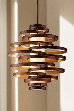 This fabulous Corbett Lighting pendant chandelier has a distinctive, modern look. The spiraling, two-tone frame is hand-crafted iron with a bronze finish on the outside and a gold leaf finish on the inside. Fixtures glow within a caramel ice diffuser bringing this design to life.