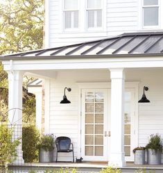 House Inspiration. Like the clean white with the black metal roof. Like the lights and the galvanized flower pots.
