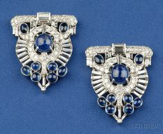 Art Deco Platinum, Sapphire, and Diamond Dress Clips, each prong-set with nine cabochon sapphires, further set with transitional and baguette-cut diamonds, approx. total diamond wt. 7.75 cts., lg. 1 5/8 in., with white gold findings and frame for brooch conversion.