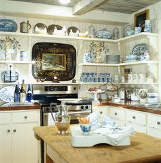 The use of open shelves display blue and white or..... Butcher block island/table adds countertop space as well as interest to the room.