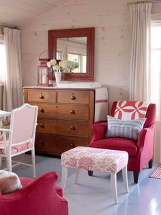 Designer Sarah Richardson combined different patterns and textures for a true cottage look in this red-and-white master bedroom sitting area. The painted knotty pine hardwood flooring and wall paneling add to the rustic look, and the experimentation with color with the furniture and accessories is a welcoming, lighthearted approach to cottage style.