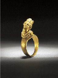 ?. A ROMAN SOLID GOLD RING WITH BUST OF THE GODDESS TYCHE 1ST-2ND CENTURY A.D. The flat hoop with bezel mounted with finely modelled bust of the goddess wearing city crown and drapery Ring: 5/8 in. (1.5 cm.) diam. max.; bust: 9/16 in. (1.4 cm.) high