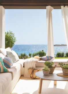 Beach house outdoor space that is inviting and relaxing with comfy pillows in the seating area