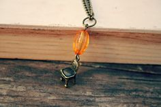 """beautiful little brass chair charm, paired with a vintage orange bead    hung on approx 18"""" bronze chain"""
