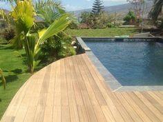 Piscine avec terrasse en bois et revêtement carrelage réalisée par Marinal.