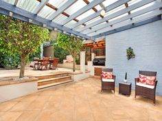 Multi-level outdoor living design with bbq area & outdoor furniture setting using pavers