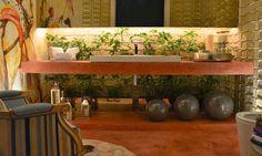 Aqui um união do bonito e prático,coisa difícil de acontecer, O jardim abaixo da bancada da pia e a iluminação é o belo e o espelho no alto (não respinga água) e sem azulejos atrás da torneira pra limpar é o prático. E a água que respingar ao usar a torneira ainda rega as plantas rsrsrs.Adorei!!! Imagem Decoração e Projetos.
