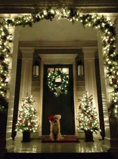 Love this Christmas porch . . . it is so much like ours, except we have a hanging light instead of wall sconces.  And, of course, we have a black cocker spaniel on our door mat!