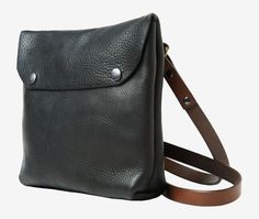 Cross over body bag with envelope flap, handmade in the UK. The black and tan…