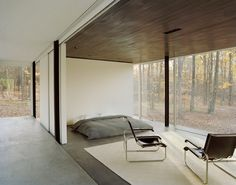 The most minimalist bedroom, but with some chairs and a rug, plus floor to ceiling windows
