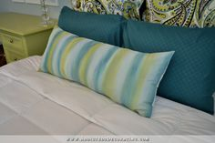 The pillow in front is one that I made using some scrap drapery lining and leftover paint.  I used three paint colors (the light blue is Rain Washed, the green is Grass Cloth, and the teal is Mosaic Tile, all from Behr) and a very watered down brush to create kind of a free form watercolor striped effect on the scrap piece of drapery lining.  I painted the fabric, let it dry completely (took about two hours), and then sewed the pillow together.