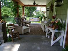 I luuuuv this front porch - the seating arrangement + ceiling fans + columns + swing