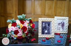 Photo frames of relatives at their weddings resting on piano with red rose petals
