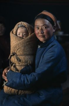 Stock Photo: 1850-22988 Mongolia, People, Young Mother In Fleece-Lined Silk Tunic Holding Baby Wrapped In Traditional Swaddling Against Bitter Winter Cold. East Asia Asian Babies Classic Classical Historical Kids Mongol Uls Mongolian Mum Older