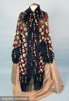 PRINTED DOLMAN JACKET, c. 1880. Black silk satin w/ multicolored velvet-flocked rose blossoms, trimmed w/ black chenille & colored ball fringes, lined in red fur plush