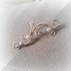 Beautiful elegant handmade adjustable unique silver plated ear cuff. These ear cuffs come with beautiful acrylic stardust metallic silver glitter beads and white glass pearls. They adjust perfectly to any size ear. No need for piercing with these cuffs as they just slip on to any ear. This listing is for one ear cuff. Please choose left /right in the dropdown menu.  *New* Your ear cuff will arrive in a lovely little box as shown in the last picture. Ideal for a gift.  See more ear cuffs in…