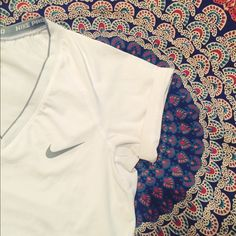 White Nike Pro VNECK Great condition. One little dash as pictured . I'm sure you could get it out with stain remover. Priced accordingly. No trades . Nike Tops Tees - Short Sleeve