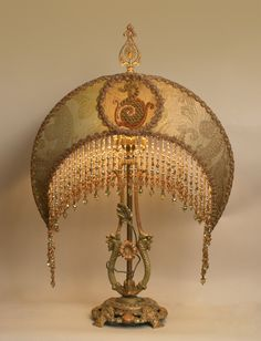 Wonderful 1920s cast lamp with dragons and roses holds a Sea Dragon Crescent in dusty sea foam green and golds. Shade is covered in beautiful antique metallic shot silk and the center panels have old sea dragon appliques. European glass and crystal hand beaded fringe adorns the bottom of the shade.