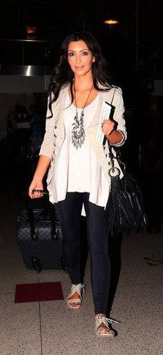 Kim and Khloe Kardashian, along with Kim`s boyfriend Reggie Bush, prepare for departure at Los Angeles International airport (LAX).
