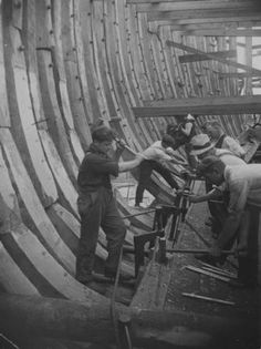 How a wooden ship is built-a photographic story of a great wartime industry. A close-up of wooden ship riveters at work-pinning together the ribs and the heavy timbers of the floor and inner hull.