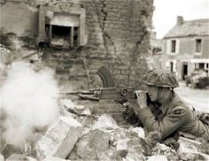 Private W Wheatley of 'A' Company, 6th Battalion Durham Light Infantry, 50th Division, fires his Bren gun from a ruined house in Douet, near Bayeux, 7 June 1944.