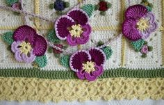 Crochet pansy bunting. Pansies based on pattern found for the Pansy Doily here: http://web.archive.org/web/20070824234331/http://www.countryyarns.com/pansy.htm