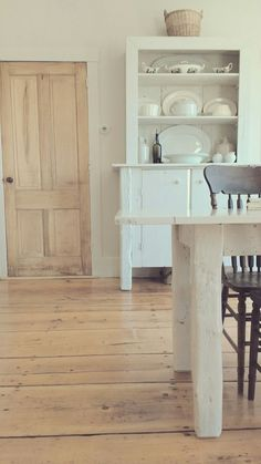 Wide plank pine floors and white furniture. Simplistic farmhouse style.