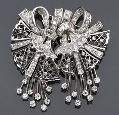A diamond double clip brooch each designed as a scrolling and lattice work ribbon of round brilliant, single and baguette-cut diamonds; accompanied by fitted box; estimated total diamond weight: 5.25 carats; mounted in platinum.
