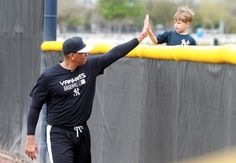 Feb 24, 2015; Tampa, FL, USA; New York Yankees third baseman Alex Rodriguez (13) high fives a young fan over the outfield fence as he runs during spring training at Yankees Minor League Complex. (Kim Klement-USA TODAY Sports)