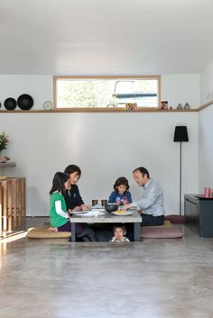 The family sits around, and under in the case of four-year-old Kaz'ma, the sunken table for a snack. Makiko made the covers of the mats her mother sent from Japan by hand. The black lamp is from Ikea.