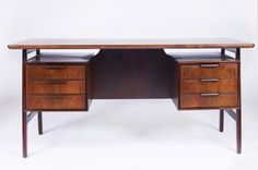 Rosewood writing desk designed by Gunni Omann and produced by Omann Jun Møbelfabrik 1960s. Beautiful floating top Rosewood desk with wonderful grain quality. The rear of the desk has storage including a drop down compartment door. This desk is elegant, produced with great craftsmanship and design throughout. It has six drawers, with very sculptural handles.  H - 740  W - 1550 D - 840   Price £2,500