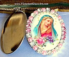 $79 Porcelain cameo locket / pendant featuring The blessed mother Virgin Mary as Our lady of Sorrows, with pink roses and purple flowers. Clear and Pink rhinestones and pink pearls. The locket is silver, possibly stainless steel, and will hold 2 pictures or a prayer petition request to Mary. Very good vintage condition.