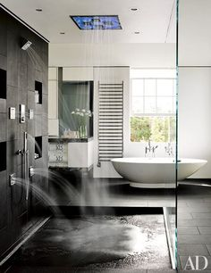 A sleek master bathroom with a free standing tub and a rain-shower system | archdigest.com