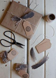 Kreative Geschenkverpackung mit Federn, Naturgarn und bestempelten Geschenkanhängern.
