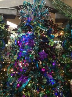 Beautiful professionally decorated Christmas tree - peacock, deep purple, turquoise, green, blue, some pinks, ice blue, basically all shades of purple, blue, and green. this is my personal favorite and the pic doesn't do it justice! Display at The Christmas Store (Decorator's Warehouse) in Arlington.