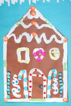 "Paper gingerbread was iced with thick white tempera.  Shingles, doors and windows were outlined with the tempera ""frosting.""  Dot daubers were used to add festive candies."