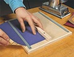 Sandpaper cutter. Simple and effective. Consists of a base board, a stop board, and a fine tooth hacksaw blade.