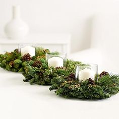 Incense Cedar Candle Ring Trio - Each ring is made from fresh, fragrant Christmas greens—noble fir, princess pine and incense cedar. Adorned with rustic pine cones, these rings surround a hurricane glass and lovely cream pillar candle to create a magical mood for your dinner.