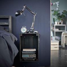 IKEA KNAGGLIG Kasten als Ablagetisch an der Wand neben einem Bett befestigt.