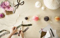 Materiais de papel dispostos sobre a mesa para fazer decorações para uma festa