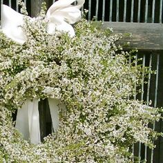 A wreath of all white heather tied with a luxurious white bow. - love these for the church doors and reception doors