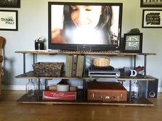Industrial/steampunk style DIY TV stand. Made with galvanized pipe and oxidized boards. Easy and cheap to make but very sturdy.
